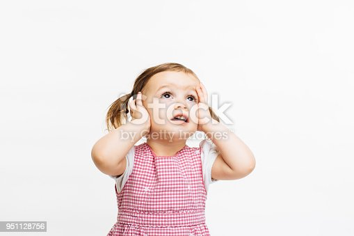 istock Oh no! Small child looking up holding her head 951128756