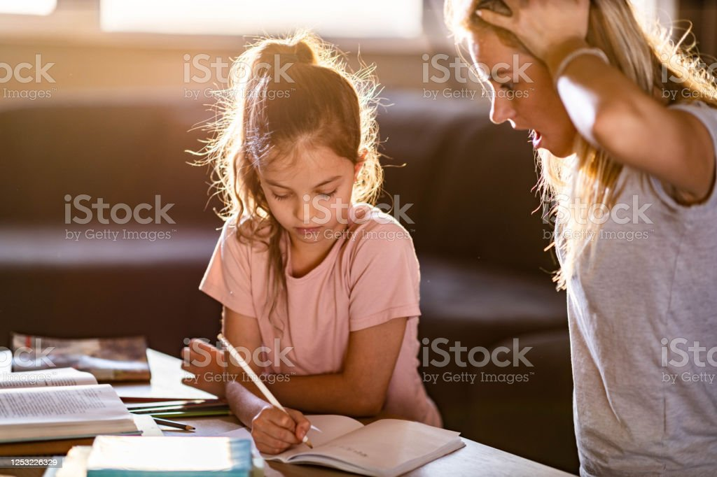 Oh no, what a shocking mistake you have written! Small girl writing her homework while her mother is looking at it in disbelief. Adult Stock Photo