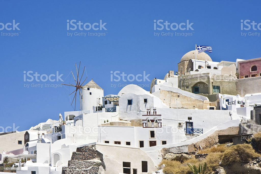 Oia city with windmill and greek flag royalty-free stock photo