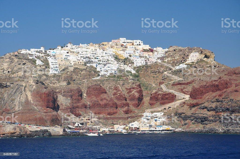 Oia cliff village, Santorini red rock and harbor stock photo