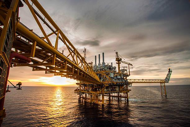 Plataforma de petróleo e gás durante o nascer ou do pôr-do-sol - foto de acervo