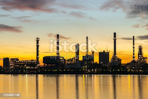 istock Oil and gas refinery industry plant with glitter lighting and sunrise in the morning, Factory of petroleum industrial, Power plant,Energy power station area. Industry 4.0 1204631182