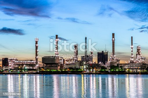 istock Oil and gas refinery industry plant with glitter lighting and sunrise in the morning, Factory of petroleum industrial, Power plant,Energy power station area. Industry 4.0 1207216240