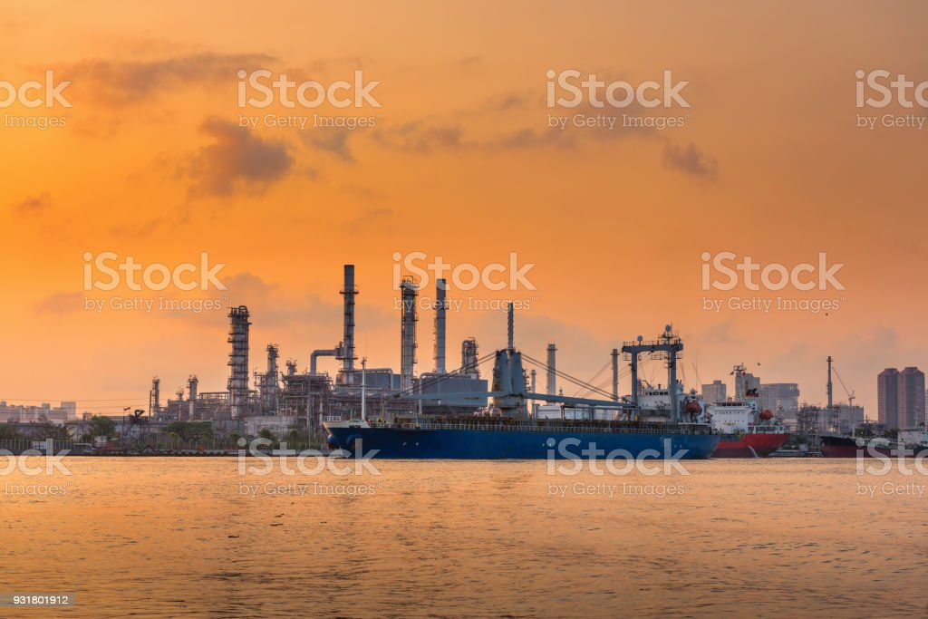 Oil and gas refinery plant with shipping loading dock at sunrise stock photo