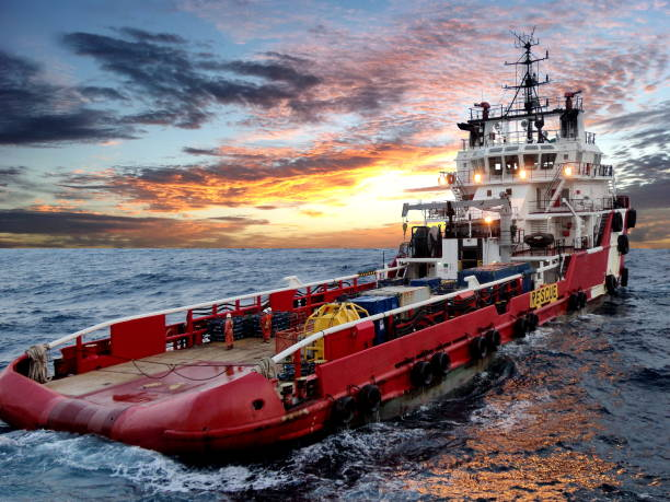 Oil and gas supply vessel in the rough sea with sunset sky in the background stock photo