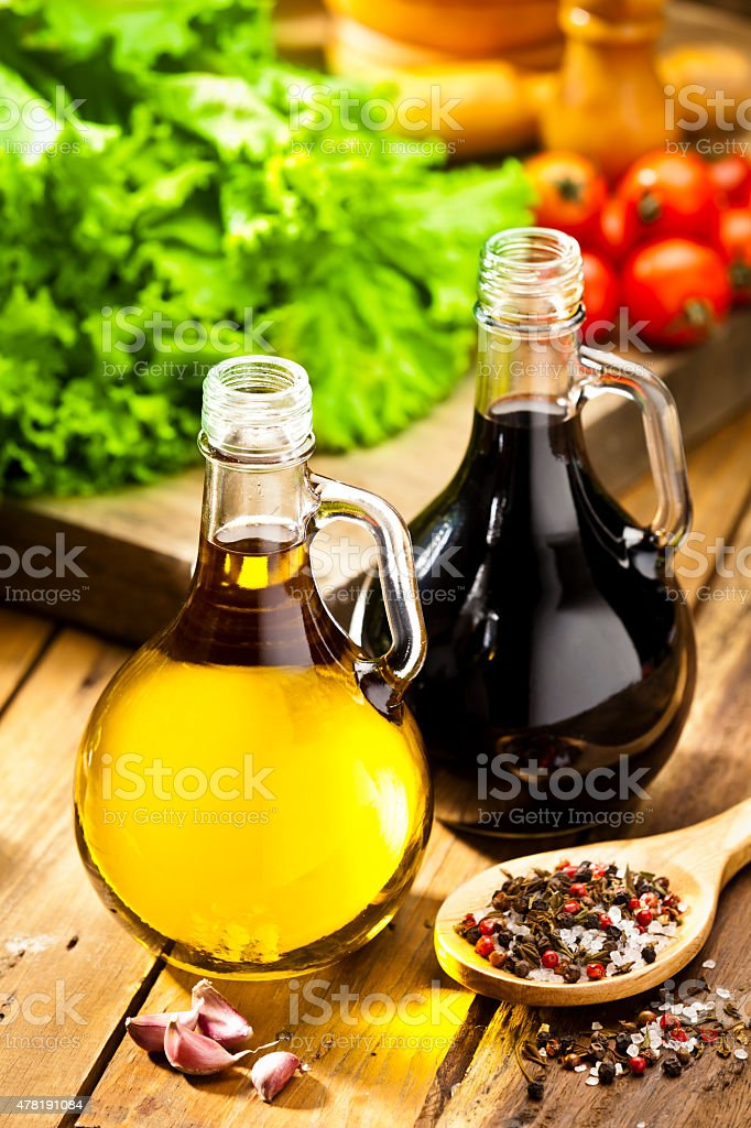 Oil and vinegar bottles on rustic wood table stock photo