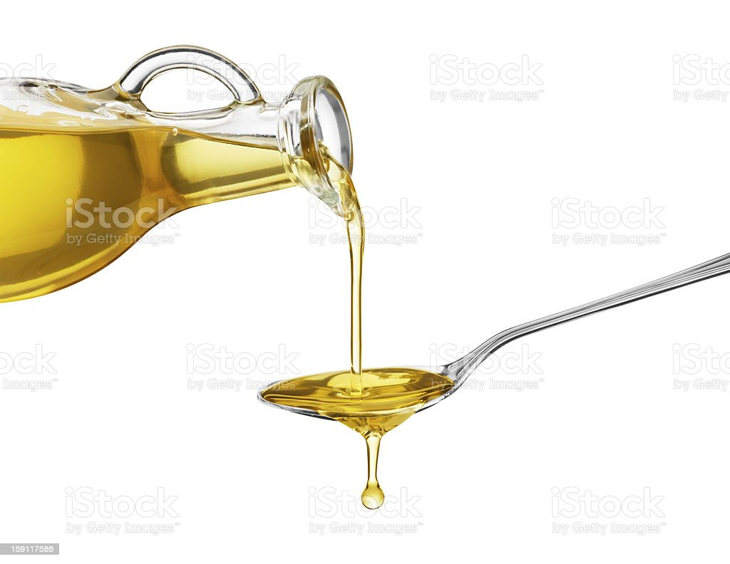 Oil being poured from a large bottle onto a spoon stock photo