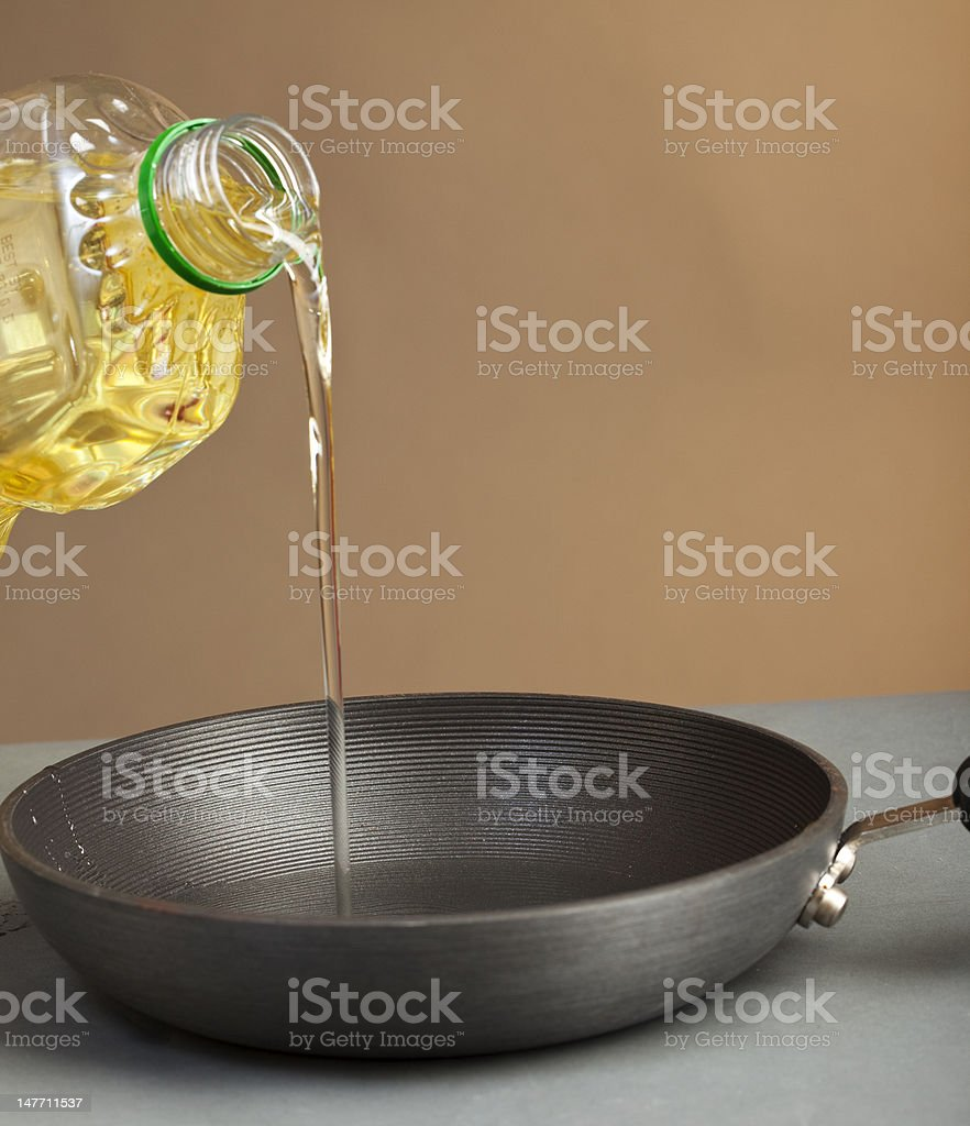 Oil Being Poured in a Nonstick Pan for Cooking stock photo