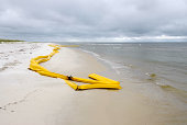 Oil protection boom used for oil spill containment pushed ashore by high winds