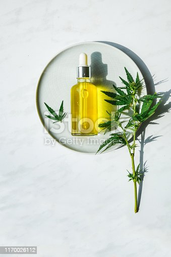 istock CBD Oil bottle and dropper on a small plate and on a marble surface. Cannabis leaves nearby. 1170026112