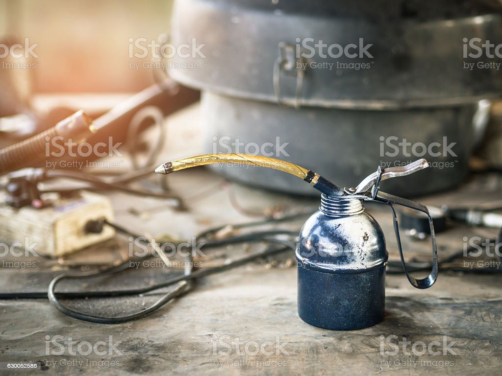 Oil can on wooden table in the garage. stock photo