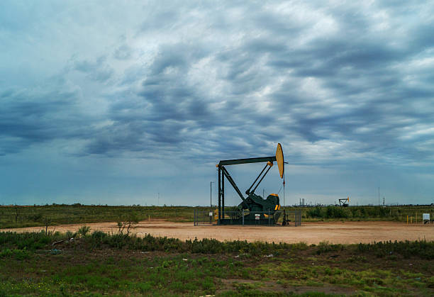 Oil derrick in west Texas with landscape stock photo