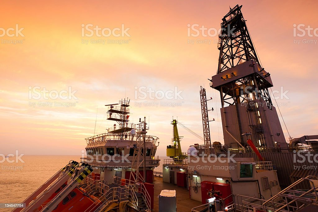 oil drill platform sailing in sunset royalty-free stock photo