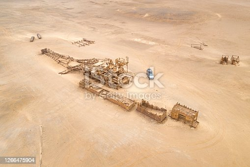 Collapsed Oil Drill Tower Rig, Skeleton Coast, Namibia. Car has been redesigned in Photoshop. Important aspect of the picture to see the scale.