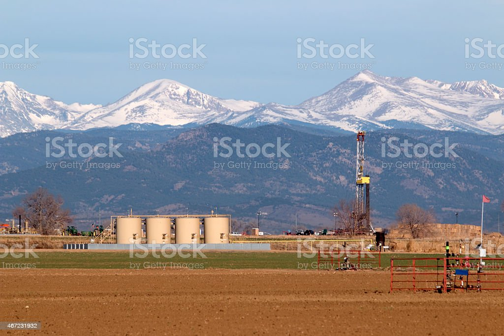 Oil drill with well pad tanks snowy Indian Peaks Colorado stock photo