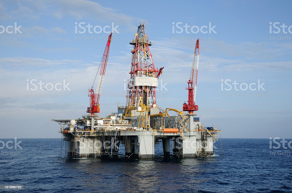 A deep water semi-submersible oil rig anchored in blue ocean. A...