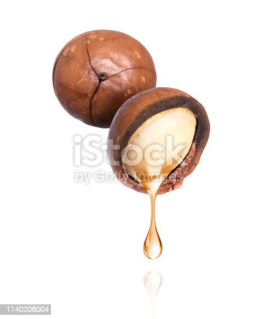 istock Oil dripping from macadamia nut, isolated on a white background 1140208004