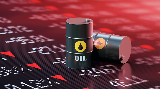 Oil drums sitting over a trading board which shows a stock market crash. Selective focus. Horizontal composition with copy space.
