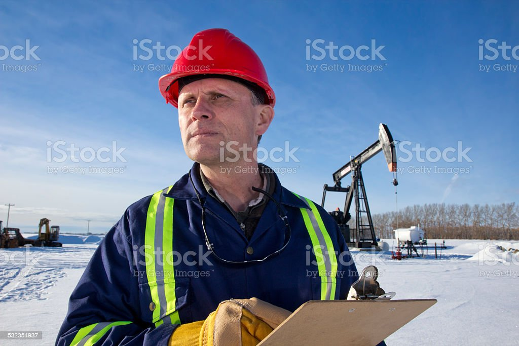 Oil Engineer at a Pumpjack stock photo