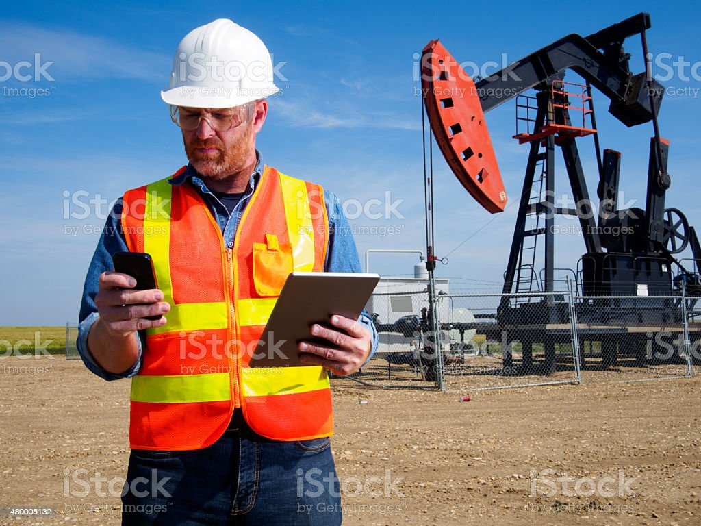 Oil Engineer with Tablet Computer and Pumpjack stock photo