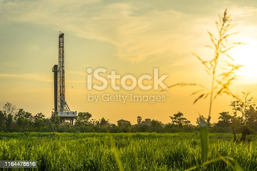 Oil field, Onshore drilling rig is drilling downhole to explore crude oil in Petroluem industrial business. The rig is operate on land in countryside area, so it arounded with beautiful agriculture field and sunlight from evening time.