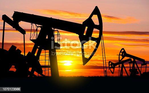 Industrial landscape.  Oil pumps against the setting sun.