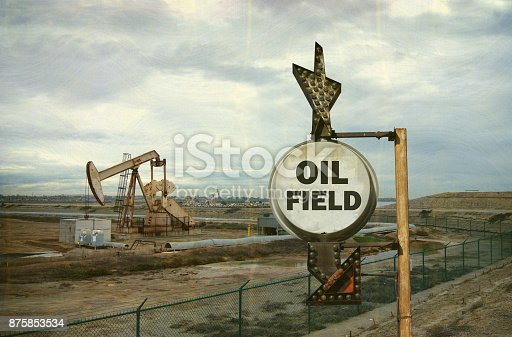 aged and worn photo of oil field with sign