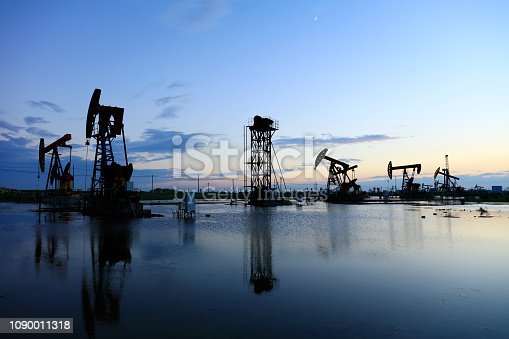 Oil fields in the evening, oil field derrick in the evening,  sunset and sunset