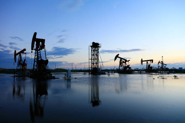 oil fields in the evening, oil field derrick in the evening,  sunset and sunset - benzina foto e immagini stock