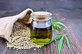 Hemp oil in a glass jar with grain in a bag, leaves and stalks of cannabis on the background of a dark wooden board