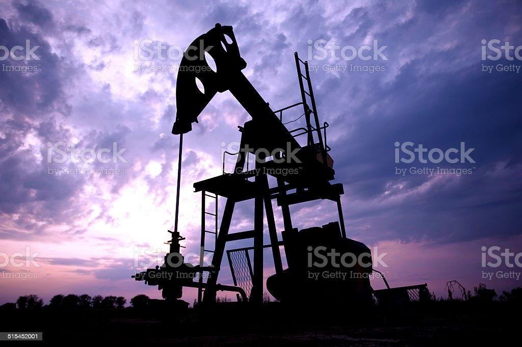 Oil horse head pump on field stock photo