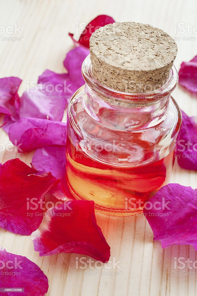 oil in glass bottle and rose petals stock photo