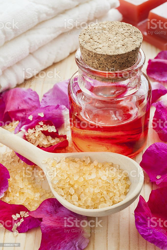 oil in glass bottle, sea salt, towel and rose petals stock photo