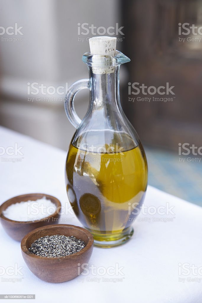 Oil in glass pitcher with bowls of salt and pepper, close-up Lizenzfreies stock-foto