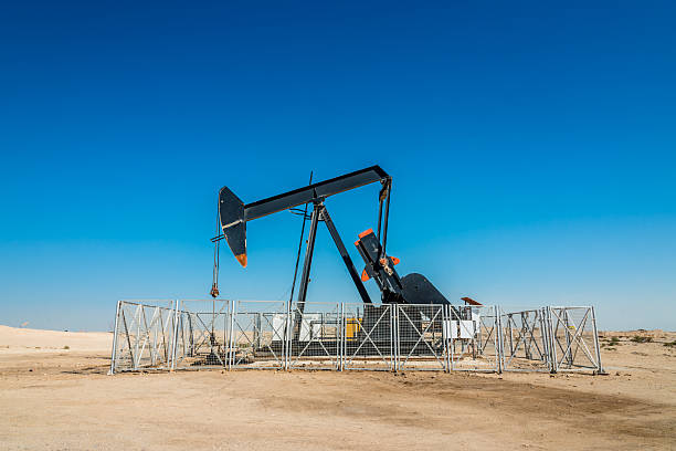Oil Industry Well Pump Oil industry well pump under blue desert sky, nodding donkey rig pumping crude oil up from the ground of an oil field in the desert. saudi arabia stock pictures, royalty-free photos & images