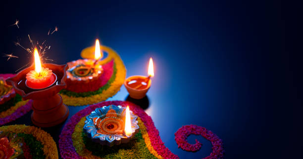 oil lamps lit on colorful rangoli during diwali celebration - diwali stock pictures, royalty-free photos & images
