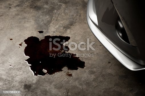 Oil leak or drop from engine of car on concrete floor , check and maintenance auto service