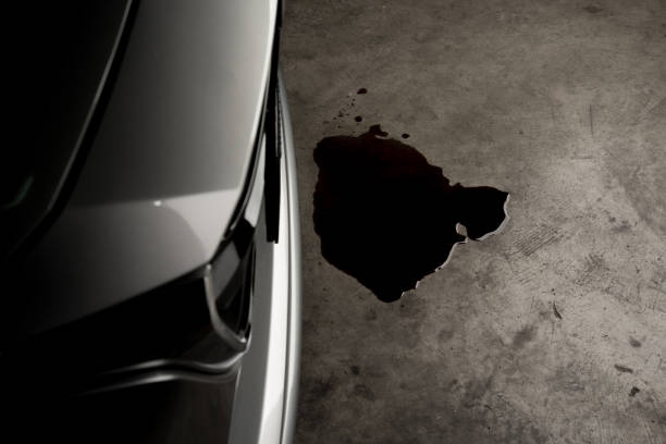 Oil leak or drop from engine of car on concrete floor , check and maintenance auto service stock photo