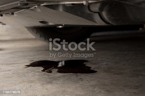 istock Oil leak or drop from engine of car on concrete floor , check and maintenance auto service 1154776379