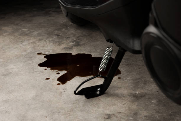 Oil leak or drop from engine of motorcycle on concrete floor , check and maintenance stock photo