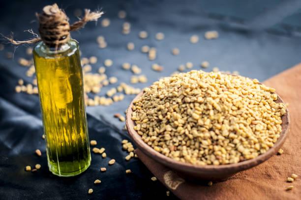 huile de trigonella foenum-graecum, methi, fenugrec dans un bol en argile avec ses graines. - fenugrec photos et images de collection