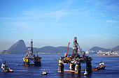 Two oil platforms in Guanabara bay surrounded by four towboats.
