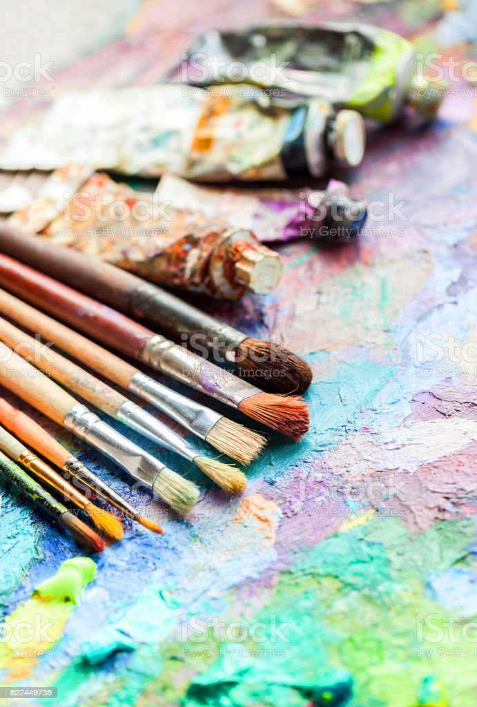 oil paints and paint brushes on a palette stock photo