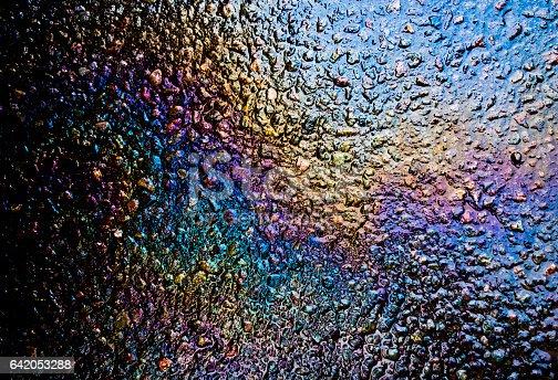 istock Oil Petrol Rainbow Slick on Tarmac 642053288