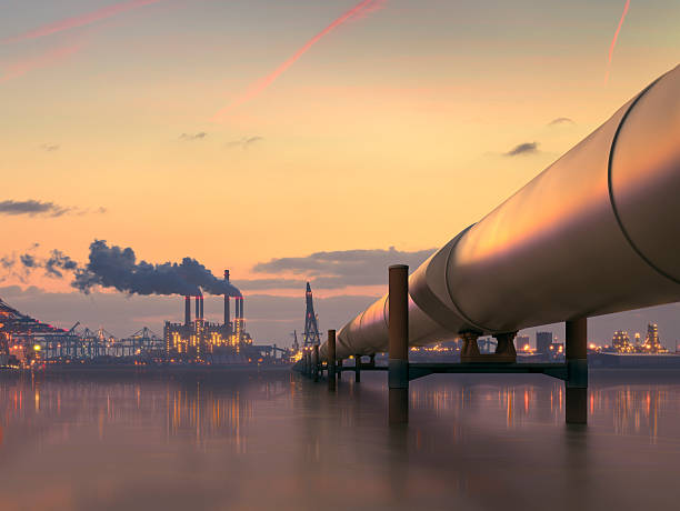 Oil pipeline in industrial district with factories at dusk stock photo