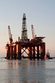 Red oil platform at sunset at exit from harbor. Baltic sea. In background of photo is a sailing ship.