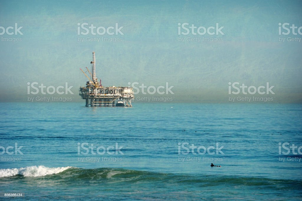 oil platform and lone surfer in ocean