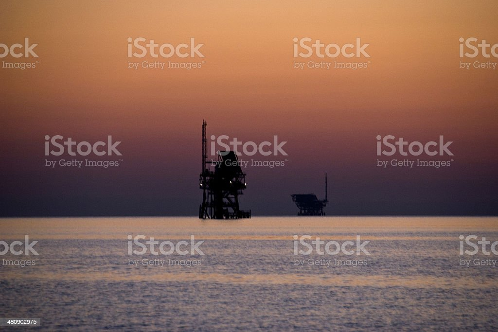 oil platforms and sunset royalty-free stock photo