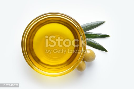 Glass bowl with olive oil on white background