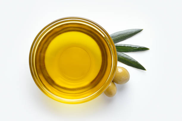 oil prepared to consume Glass bowl with olive oil on white background olive oil stock pictures, royalty-free photos & images